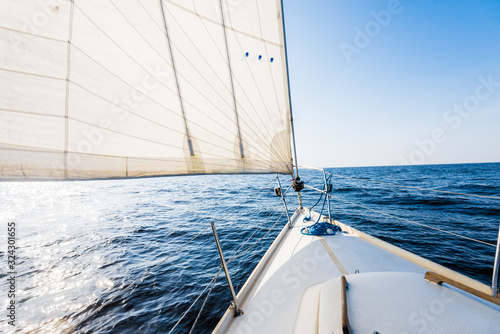 White yacht sails on a clear sunny day. A view from the deck to the bow and sails, close-up. Baltic sea, Latvia