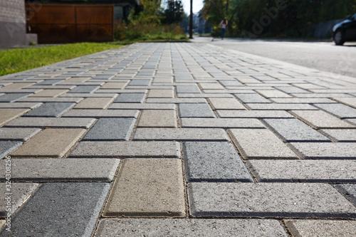 Fotografie, Obraz Colorful cobblestone road pavement and lawn divided by a concrete curb