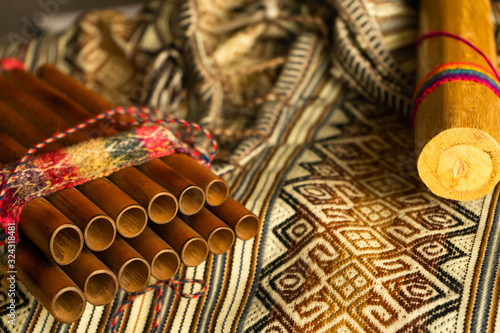 Fototapeta Close up view of Peruvian pan flute and rain stick on traditional colorful textile