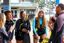 Diving Instructor Helps A Beginner Diver Prepare For Diving. Diver Team, Instruction And Training