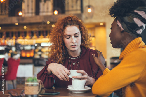 A young woman is talking with a female friend about her problem in a cafe. The friend is supportive and understanding.
