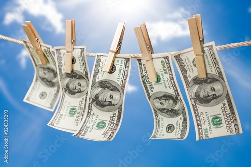 Fotografering American dollars in a rope on sky background