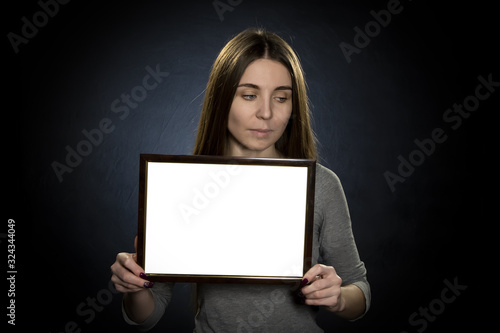 Photo Portrait of a Young woman 25-30 years old holding a white text frame on a dark b