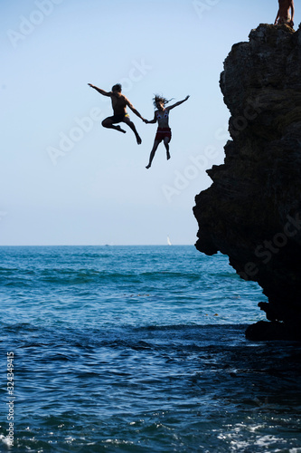 Photo Boy and Girl jumping off a cliff into the ocean