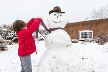 A Six Year Old Boy Building A Snowman