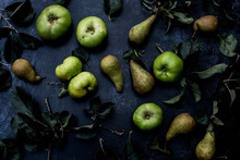 High Angle Close Up Of Green Pears And Bramley Apples On Black Background.