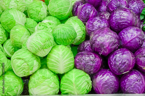 Fototapeta Assortment of organic red and green cabbage heads close-up at farmer market obraz