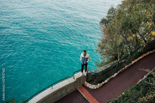 Photo Young man standing on the stone near Mediterranean sea with azure water in Monaco