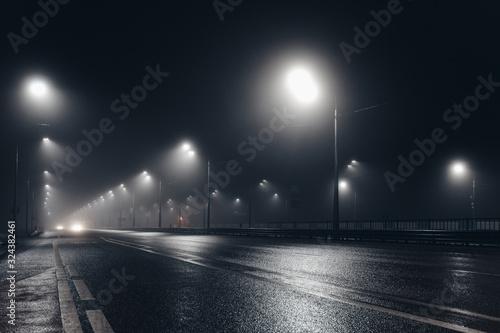 Foggy misty night road illuminated by street lights Canvas Print