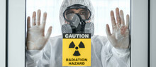 Scientist With Coverall Protection Clothing And Full Face Protection Mask In Control Room With Radiation Hazard Sign