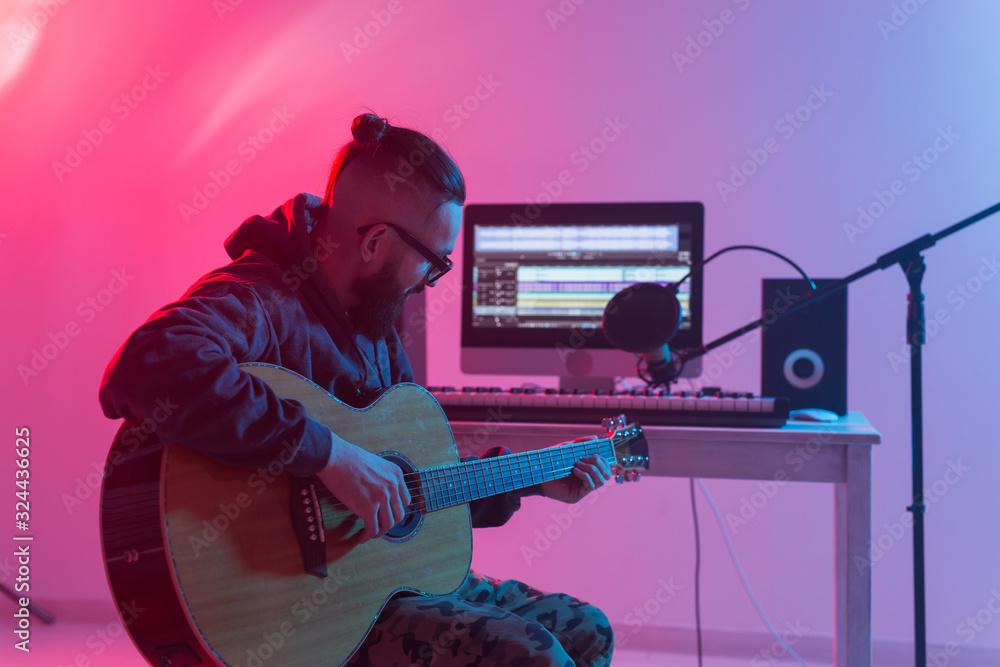 Fototapeta Create music and a recording studio concept - Bearded funny man guitarist recording electric guitar track in home studio