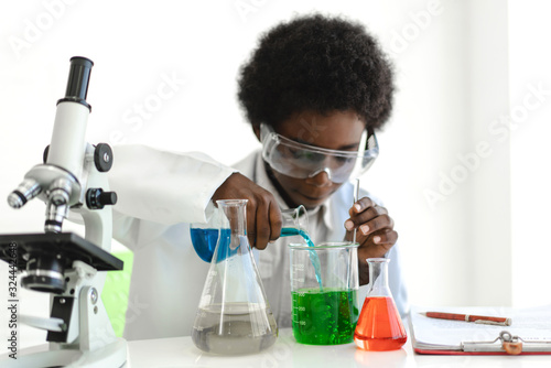 Fototapeta African american boy students learning and doing a chemical experiment and holding test tube in hands in science class on the table.Education concept obraz