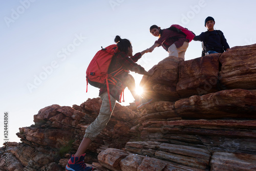 Fototapeta silhouette male and female hikers climbing up  mountain cliff . obraz