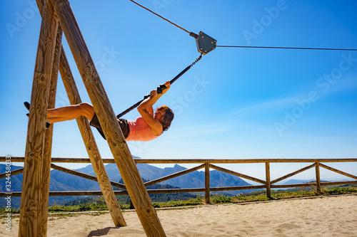 Fototapeta Adult woman having fun on zipline obraz