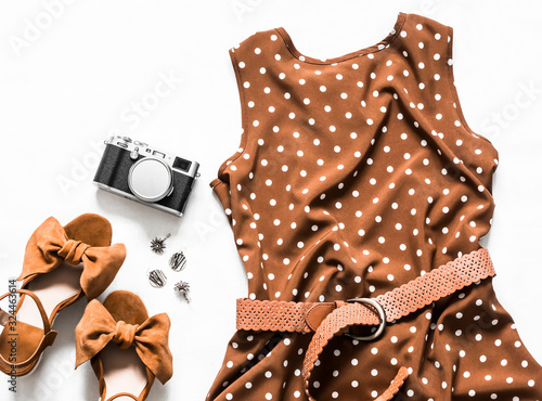 Fotografía Summer dress with polka dots without sleeves, suede wedge sandals, earrings, camera on a light background, top view
