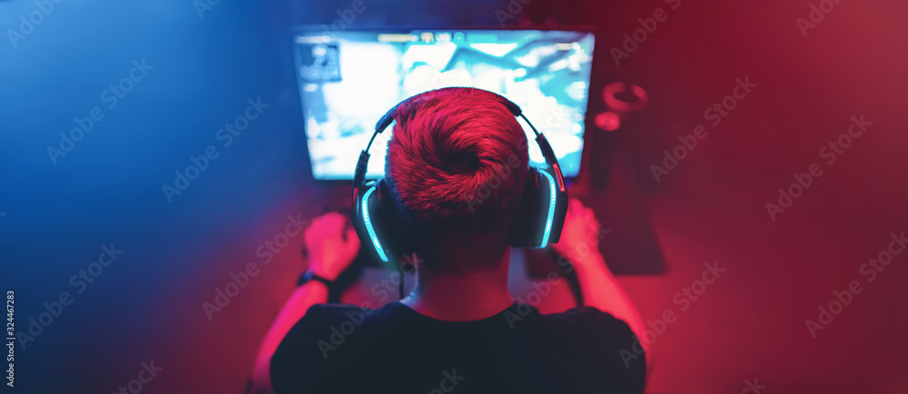 Fototapeta Blurred background professional gamer playing tournaments online games computer with headphones, red and blue