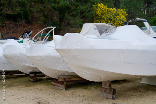 power boat parking covered white protective plastic film new modern boats in cov Tablou Canvas