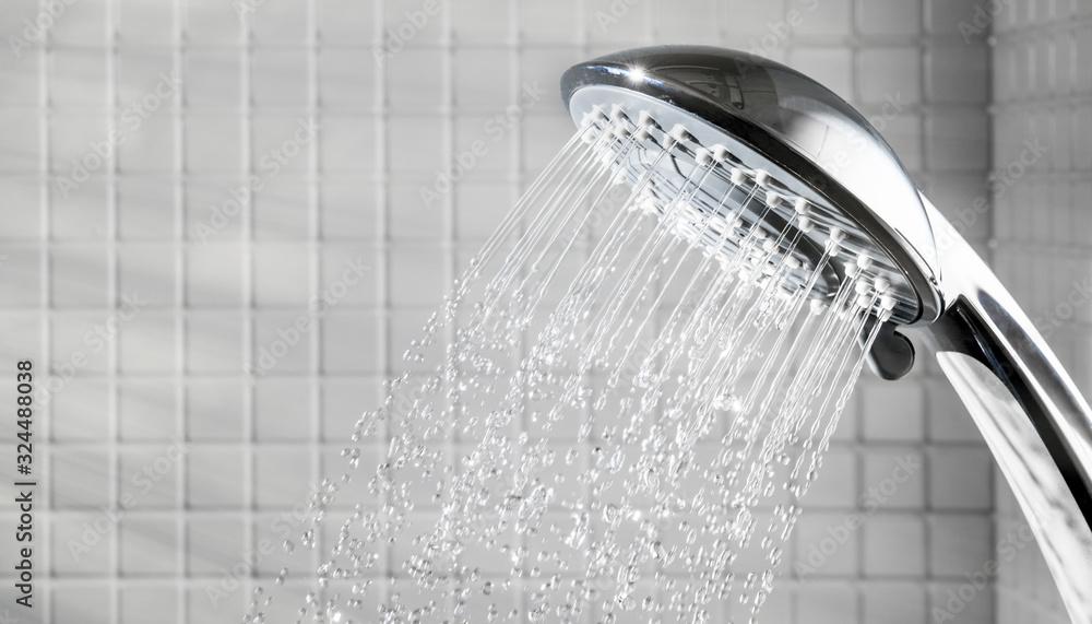 Fototapeta Shower head with running water in white bathroom