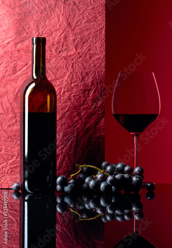 Fotomural Bottle and glass of red wine on a black table.