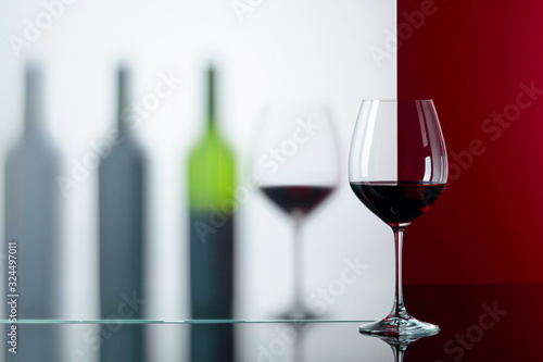 Cuadros en Lienzo Bottles and glasses of red wine on a black reflective background.