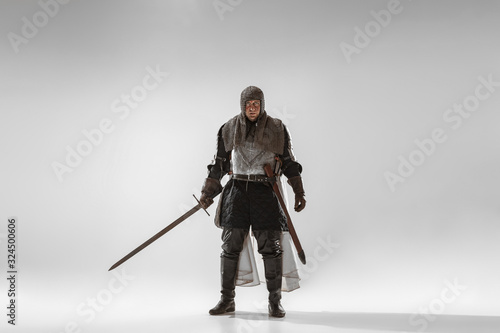 Foto Brave armored knight with professional weapon fighting isolated on white studio background
