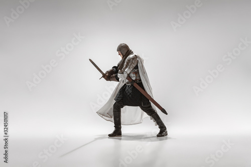 Brave armored knight with professional weapon fighting isolated on white studio background Fototapeta