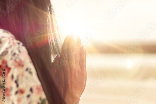 A woman praying hand for blessings When the sun goes down Hope for a happy life Fototapete