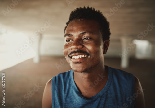Fototapeta Happy portrait of a happy young african american young athlete looking away at outdoors obraz