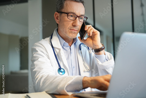 Fotografía Doctor in office working on laptop talking on phone