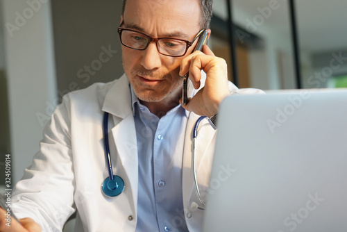 Fotomural Doctor in office working on laptop talking on phone