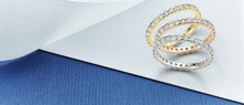 Eternity Rings On Blue And White Background. Featuring White Gold, Yellow Gold And Rose Gold Diamond Eternity Ring Banner On Blue And White Card.
