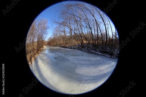 Fotografía Frozen river in forest. Circular fisheye landscape