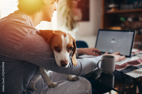 young man cuddling with his dog while drinking morning coffee and using laptop i Canvas Print