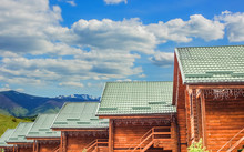 Wooden Cabin Cottages Rustic Architecture Building Foreground And Vivid Highland Landscape Background Space With Blue Sky And White Clouds Travel And Tourism Concept Advertising Picture
