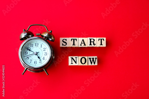 Photo start now concept with text on wooden block and alarm clock on red background
