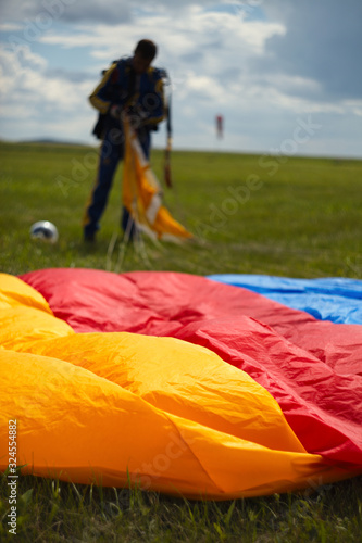 Fotografie, Obraz Canopy of the parachute in the foreground and the blurred silhouette of the skydiver after landing
