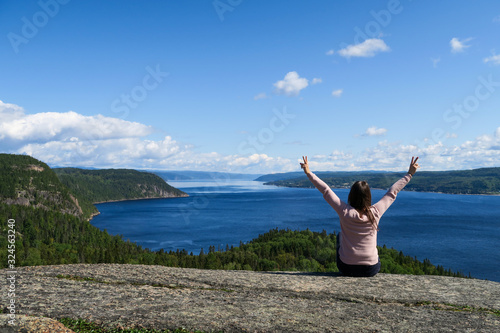 Joyful young woman sitting on a rock admiring the beautiful Saguenay fjord Canvas Print