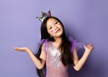 Cute Asian Kid Girl Princess In Party Dress And Crown And With Painted Red Hearts Is Holding Hands Up With Open Palms