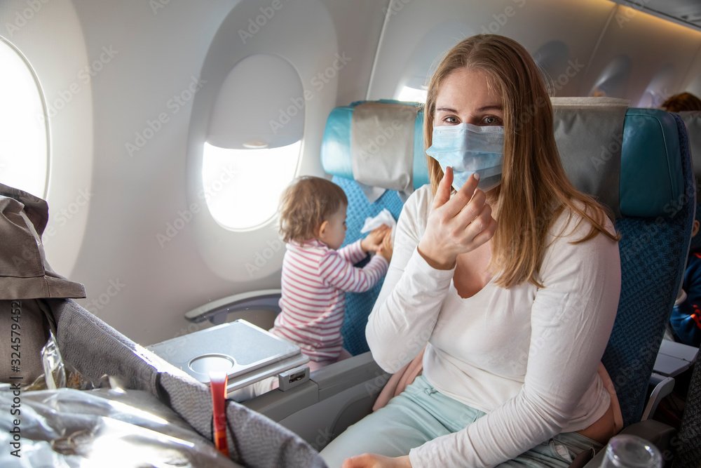 Fototapeta concept fear of travel because of coronavirus covid-19..a young mother is sitting in an airplane chair in a medical respiratory mask and sneezes. a cute baby is sitting next to her