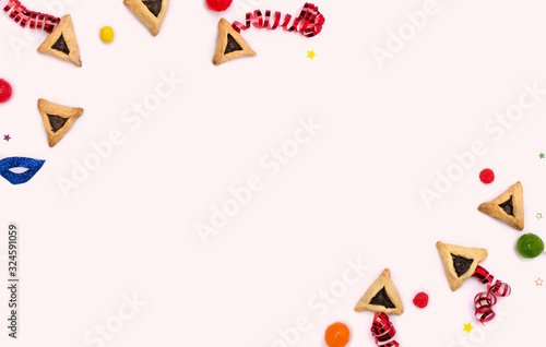 Frame of triangular cookies ( hamantasch or aman ears ), candy, mask, serpentine, confetti for jewish holiday of purim celebration on pink background with space for text Wallpaper Mural
