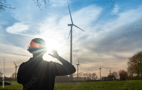 Obraz Engineer standing in front of a wind turbine during sunset. - fototapety do salonu