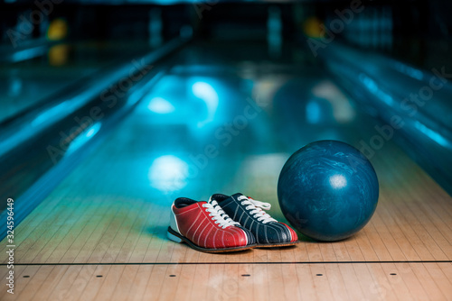 selective focus of bowling shoes and ball on skittle alley in bowling club Fototapeta