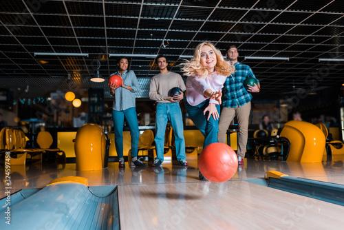 Fototapeta smiling blonde girl throwing bowling ball on skittle alley near multicultural friends obraz