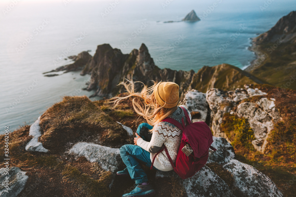 Fototapeta Woman relaxing alone travel in Norway adventure vacations healthy lifestyle backpacking Vesteralen landscape rocks and sea aerial view