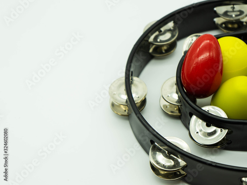 Fotografía Top view of black tambourine with egg shakers on a white background