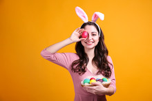 Studio Portrait Of Young Beautiful Woman Wearing Traditional Bunny Ears Headband For Easter And Smiling. Brunette Female With Wavy Hair Over Yellow Background. Close Up, Copy Space.