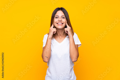Fotomural Young woman over isolated yellow background smiling with a happy and pleasant ex