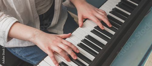 Fototapeta Teenage girl generation in headphones plays the piano, synthesizer, composes music, teenagers' hobby