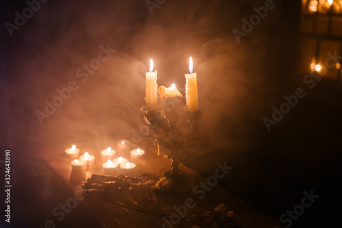 Fotografie, Obraz Antique candlestick in a mysterious atmosphere of smoke