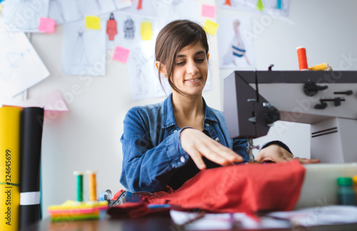 Young fashion designer sewing at workshop Tapéta, Fotótapéta